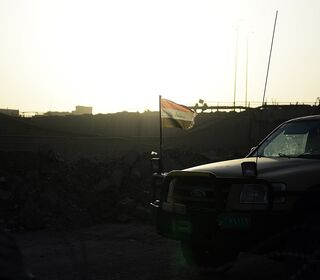 The sun rises behind a SUV with an Iraqi flag atached to it.