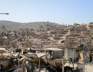 Burned hills with destroyed shelters in the refugee camp Moria, Lesbos.