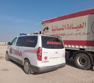 An ambulace from CADUS in front of a truck from Heyva Sor at Tal Tamr.